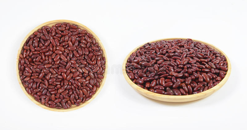Den röda bönan kärnar ur användbart för hälsa i den wood maträtten på vit bakgrund royaltyfria bilder