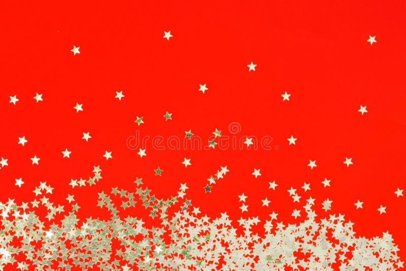 Den röda bakgrunden med blänker och försilvrar stjärnakonfettier Ljus bakgrund för festlig ferie royaltyfri foto