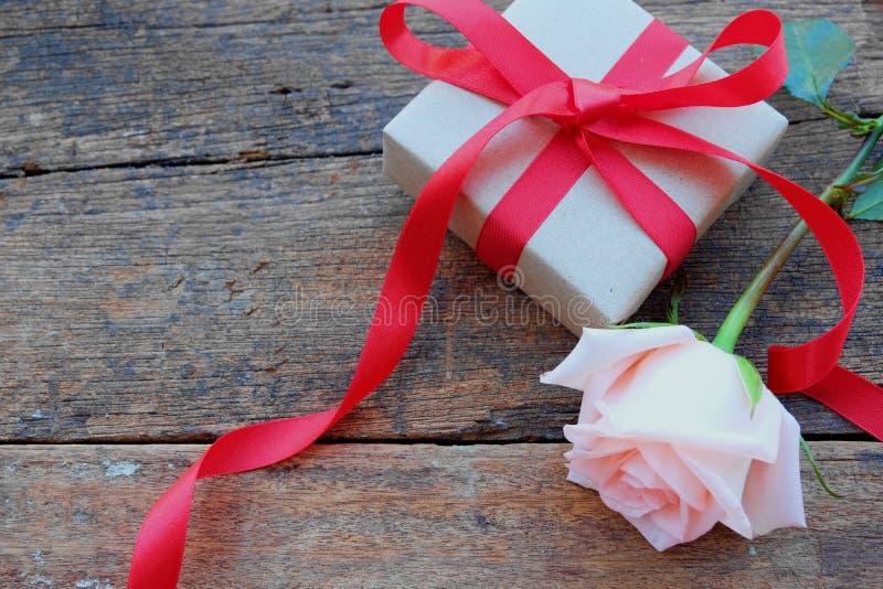 Den röda bandgåvaasken och apelsin-rosa färger steg på tappningträtabellen för Valentine& x27; s-begrepp royaltyfri fotografi