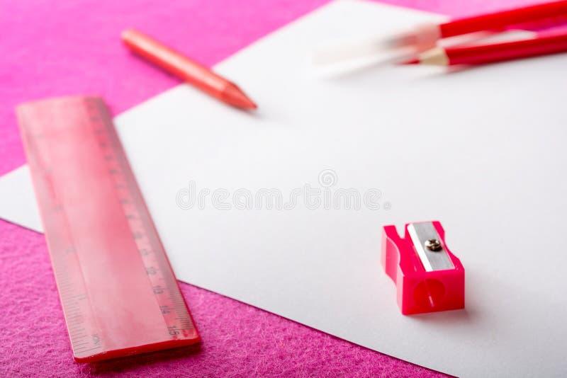 Den röda blyertspennan med den vässare-, linjal- och filtpennan på vitbok täcker Kontorshjälpmedel royaltyfri foto