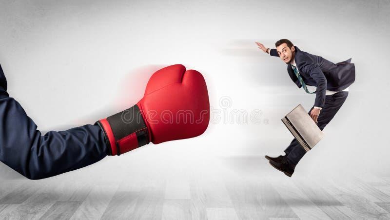 Den röda boxninghandsken knackar ut den lilla affärsmannen royaltyfri bild