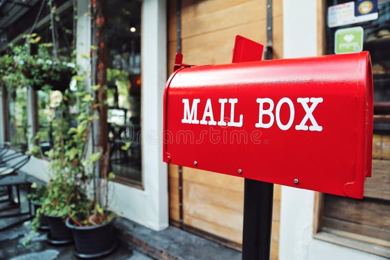 Den röda brevlådan framme av ett husbegrepp av e-komrets postar nuförtiden - kontoret ger främst sändningsservice royaltyfri foto