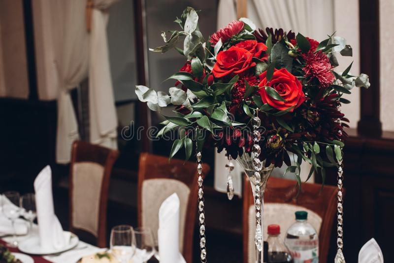 Den röda buketten i vas på tabellen på det lyxiga mottagandet för bröllop vilar in arkivbild