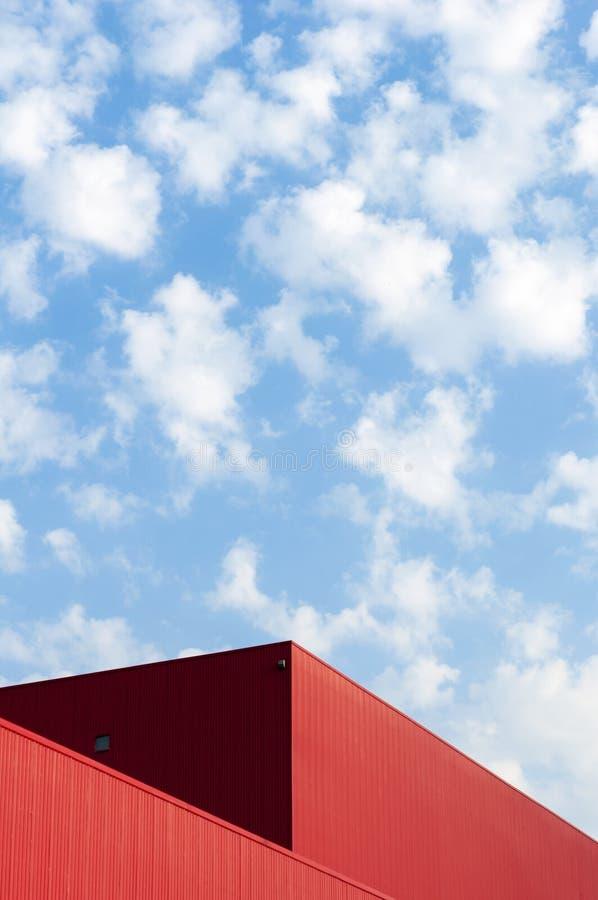 Den röda byggnaden och den blåa himlen arkivbild