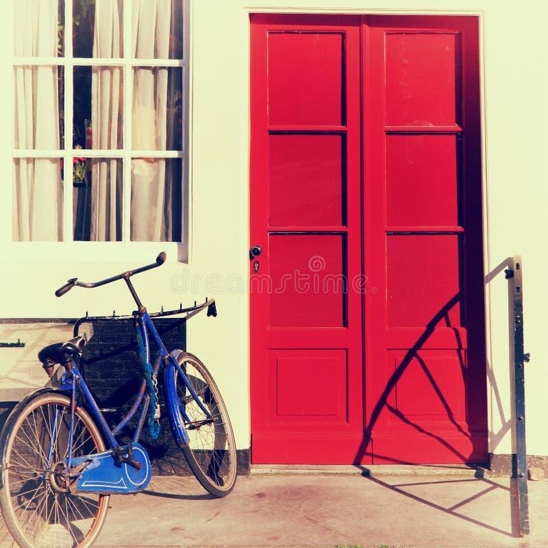 Den röda dörren och blått cyklar i det gamla europeiska huset, Amsterdam royaltyfri fotografi