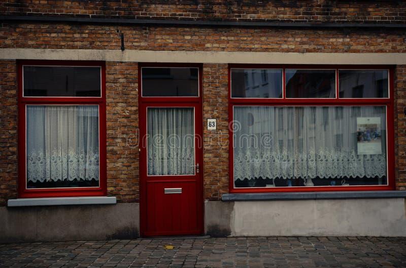 Den röda dörren och shoppar fönster på tegelstenväggen av huset i Bruges, Belgien royaltyfri fotografi