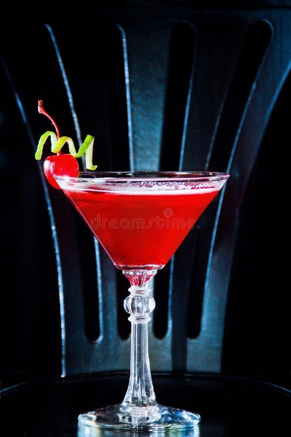 Den röda drinkcoctailen med körsbäret i martini exponeringsglas, körsbäret och limefrukt skalar arkivbilder
