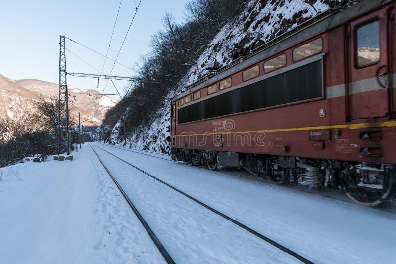 Den röda elektriska lokomotivet i vinterinflyttningsnön täckte land fotografering för bildbyråer