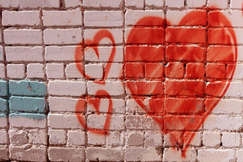 Den röda förälskelsehjärtahanden som drogs på grunge för tegelstenvägg, texturerade moderiktig gatastil för bakgrund arkivfoto