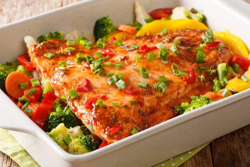 Den röda fisken filea bakat med grönsaker, kryddor och örtnärbild i en stekhet maträtt horisontal royaltyfria bilder