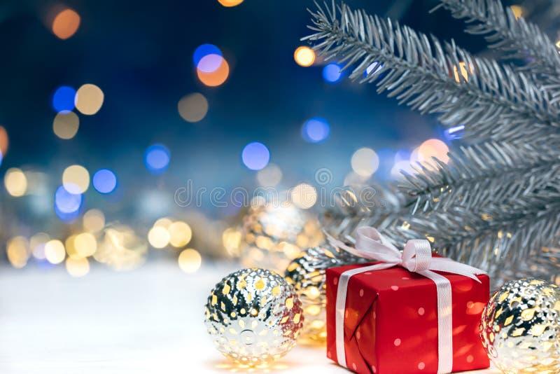 Den röda gåvaasken med garneringar för julgranträdet förgrena sig på blurr royaltyfria foton