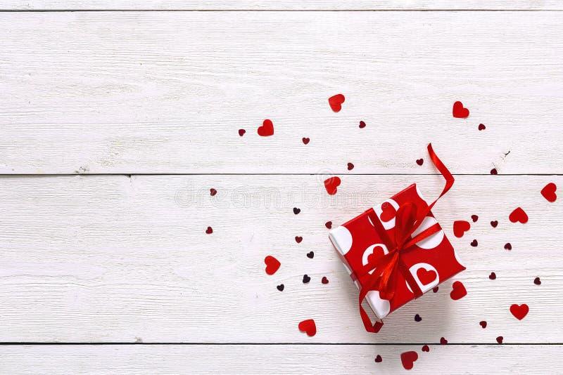 Den röda gåvaasken med pappers- hjärtor på vit målade träplankor royaltyfri foto