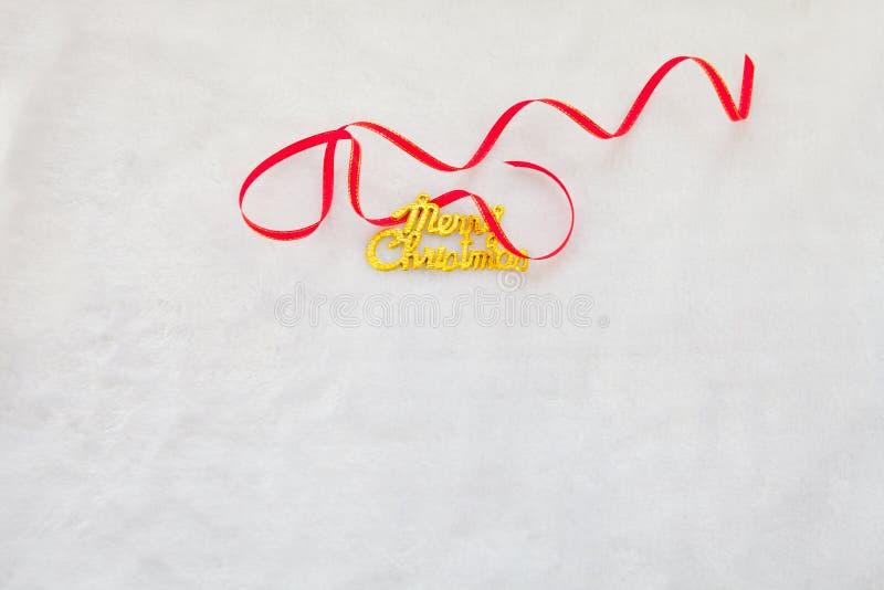 Den röda gåvaasken och guld- glad jul smsar med det röda bandet royaltyfri bild