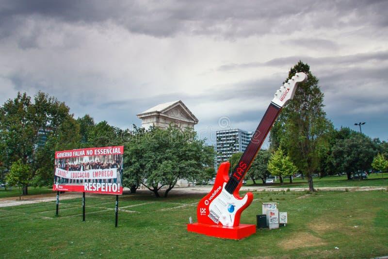 Den röda gitarren med den Vodafone annonseringen på staden parkerar i Lissabon royaltyfri fotografi
