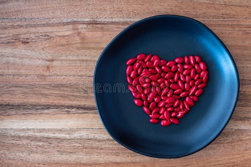 Den röda godisen täckte solrosfrö i en hjärtaform på en lantlig svart platta på en träbakgrund arkivbild