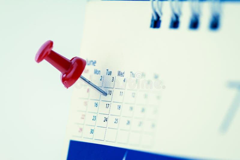 Den röda häftstiftet på kalendersidan för påminner och markerade viktiga händelser royaltyfri bild