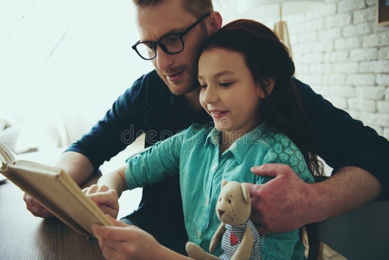 Den röda haired fadern i exponeringsglas läser boken arkivbilder