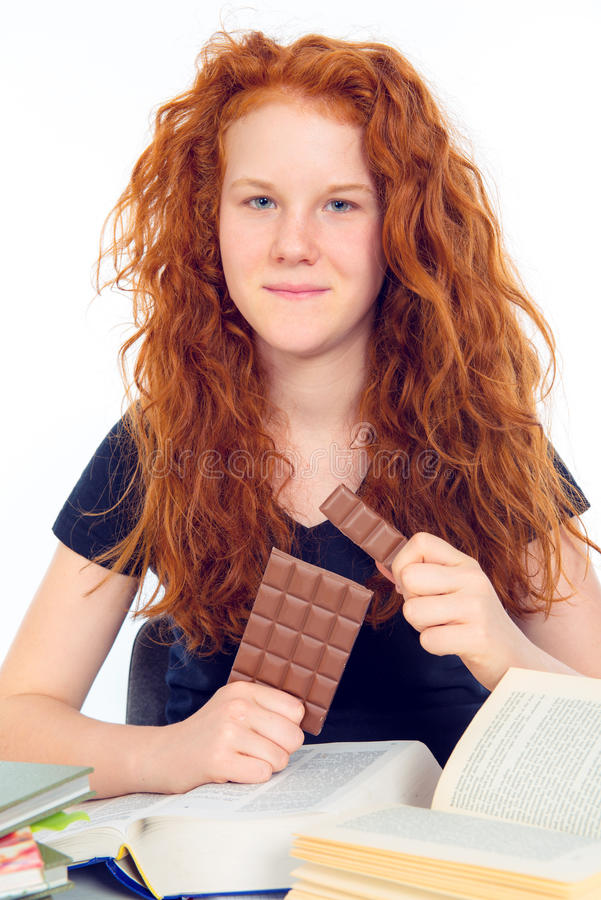 Den röda haired flickan är lära och äta choklad royaltyfri fotografi