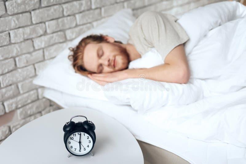 Den röda haired unga mannen sover i sovrum royaltyfri bild