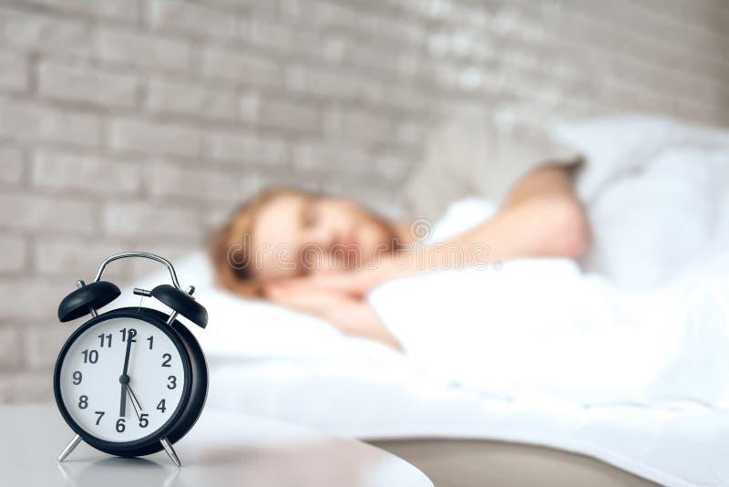 Den röda haired unga mannen sover i sovrum fotografering för bildbyråer