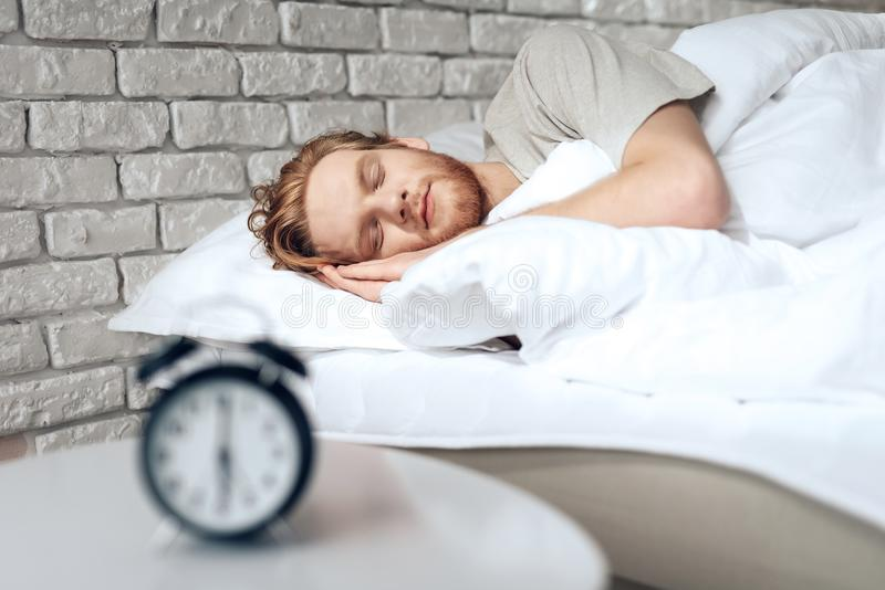 Den röda haired unga mannen sover i sovrum royaltyfria bilder