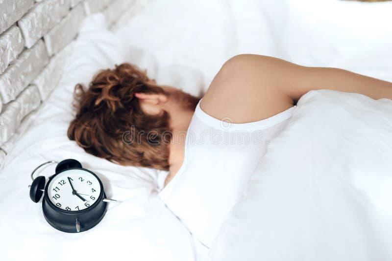 Den röda haired unga mannen sover i sovrum arkivfoton