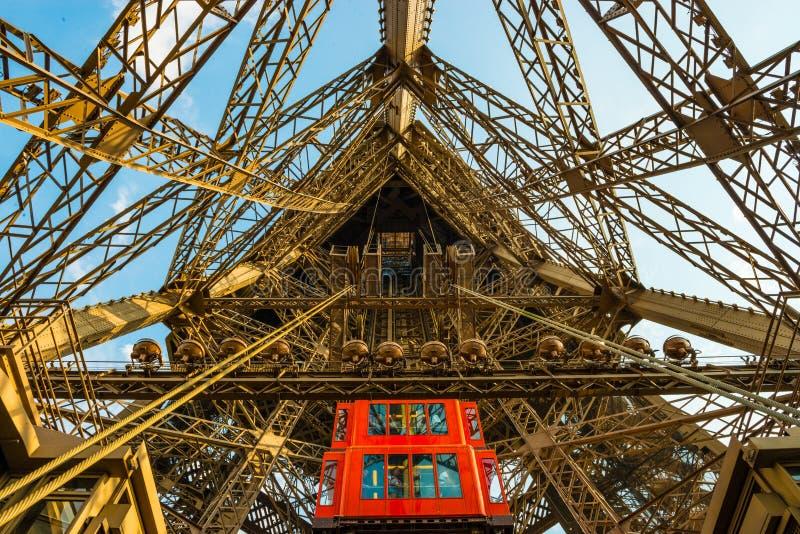 Den röda hissen kommer med turister ner axeln i metallEiffeltornstrukturen i Paris arkivfoton