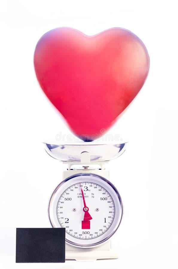 Den röda hjärtaformballongen vägas på retro den isolerade stilskalan arkivfoton