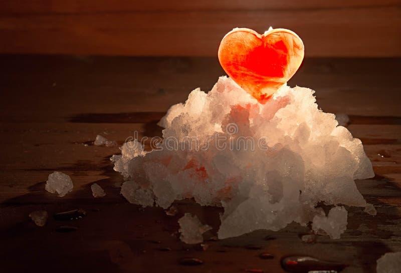 Den röda ishjärtan på en snö den lilla gruppen tände med stearinljusbrännskadan arkivbilder