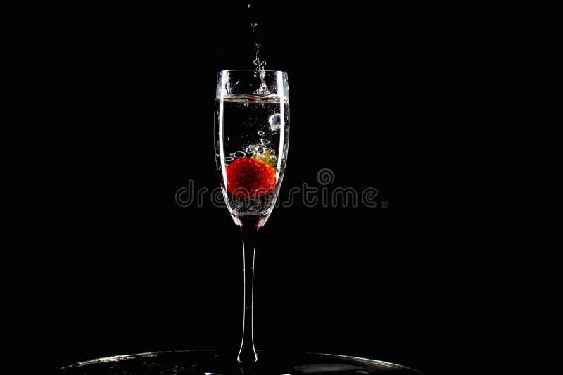 Den röda jordgubben faller in i ett exponeringsglas av vatten med färgstänk fotografering för bildbyråer