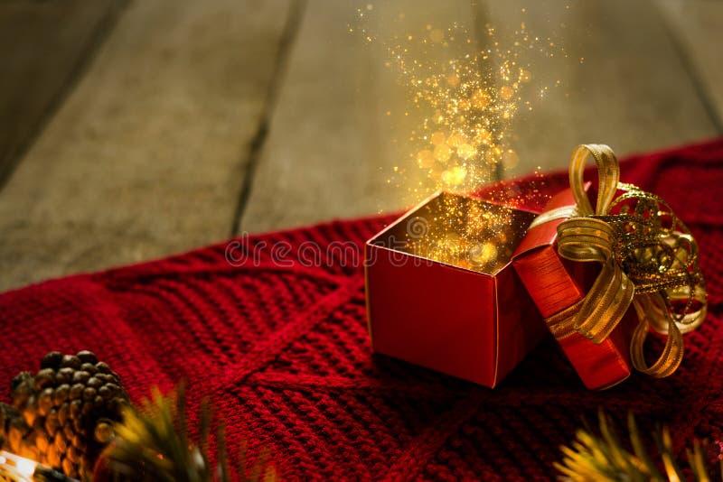Den röda julgåvaasken på röd scraf med guld- partiklar tänder magiskt på träskrivbordet arkivfoton