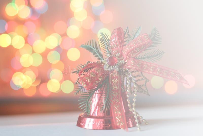 Den röda julklockan dekoreras med en pilbåge garnering för julgran på nytt år eller juldag slapp fokus royaltyfri bild