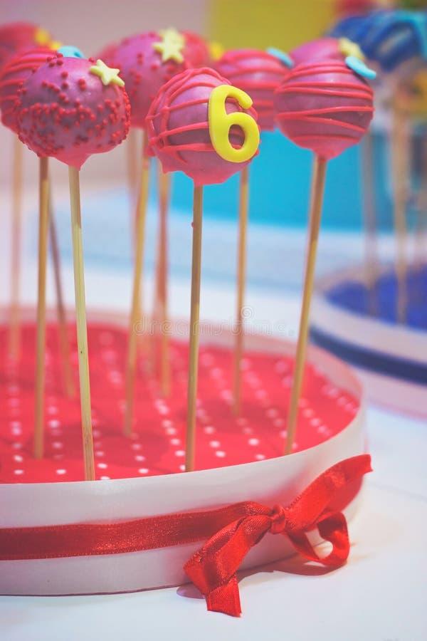 Den röda kakan poppar med födelsedaggarnering och nummer 6 fotografering för bildbyråer