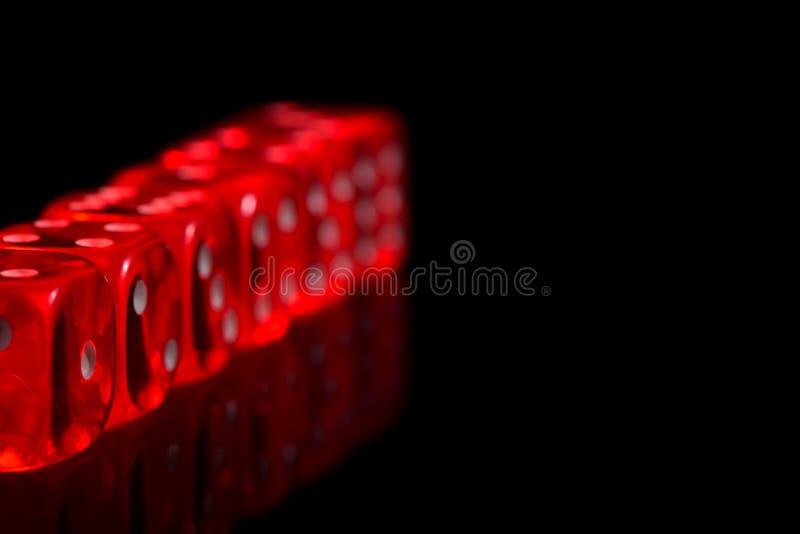 Den röda kasinot tärnar på den svart reflekterade bakgrunden arkivbilder