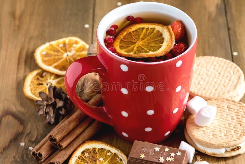 Den röda koppen av varmt te med Cinnamone för bakgrund för begreppet för apelsin- och för drycken för bärjulvinter julmat träpinn arkivbilder