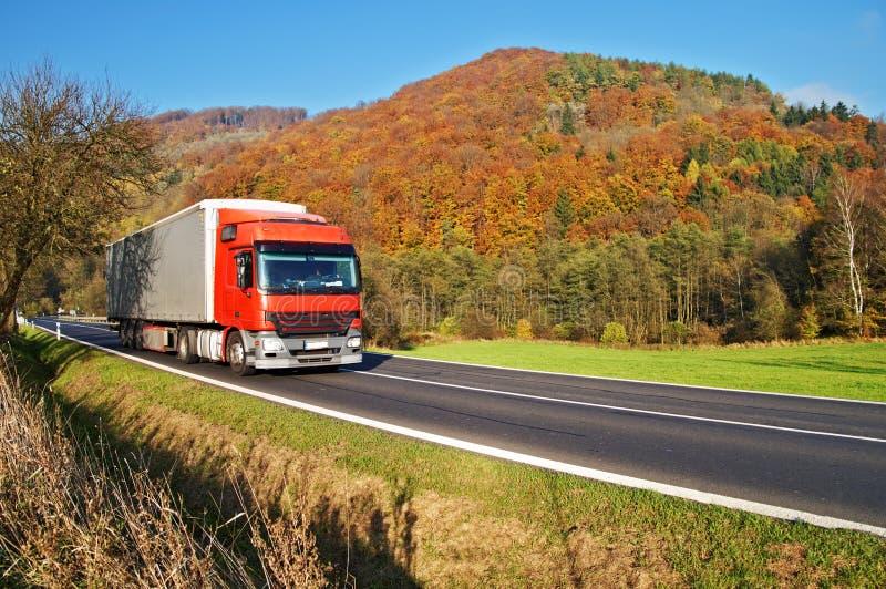 Den röda lastbilen på vägen under det skogsbevuxna berget av den färgrika hösten färgar royaltyfria bilder