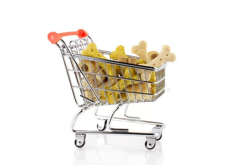 Den röda livsmedelsbutikshoppingvagnen med hunden behandlar mat bakgrund isolerad white royaltyfri bild