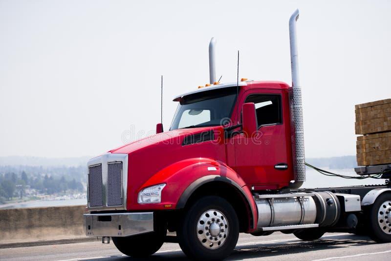 Den röda moderna halva lastbilen med dagtaxin och släpet för plan säng bär lu royaltyfria bilder
