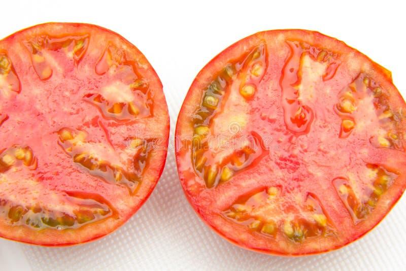 Den röda och mogna tomaten halverade arkivbild