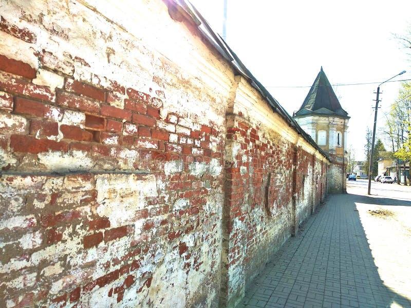 Den r?da och vita tegelstenv?ggen av kloster med en liten stad i mitten av Ryssland royaltyfri foto