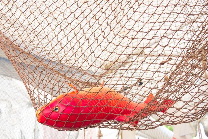 Den röda orange plast- fisken i en repfisk förtjänar arkivbilder