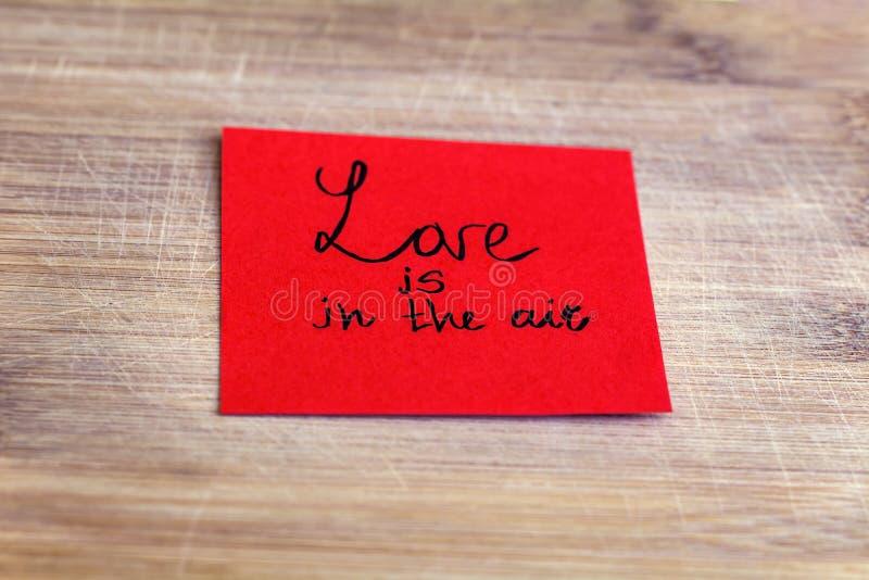 Den röda pappers- anmärkningen med förälskelse är i lufttecknet på en träbakgrund royaltyfri bild
