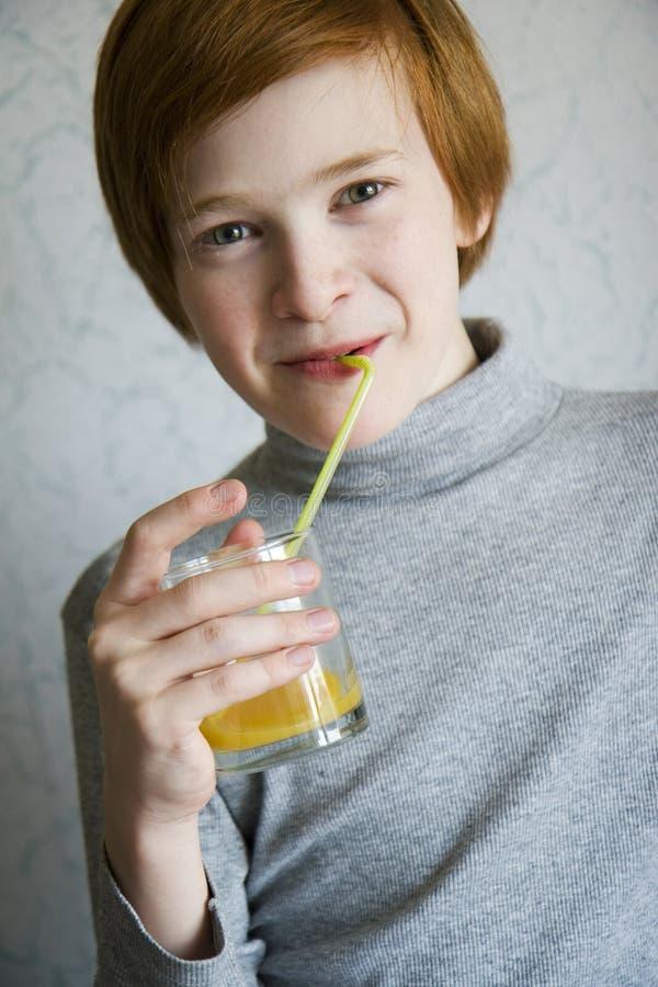 Den röda pojken dricker fruktsaft fotografering för bildbyråer