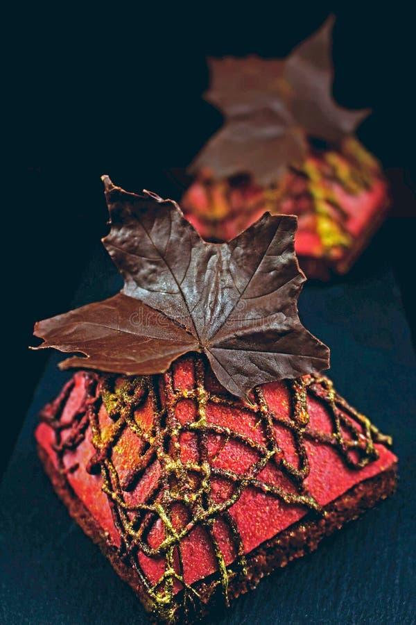 Den röda pyramiden texturerade efterrätter med chokladlönnlöv på mörk bakgrund arkivfoton