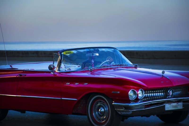 Den röda retro bilen på den Malecon sjösidan i blått glöder royaltyfria foton