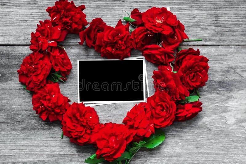 Den röda rosen blommar hjärta som formas med den tomma fotoramen på lantlig träbakgrund royaltyfria foton