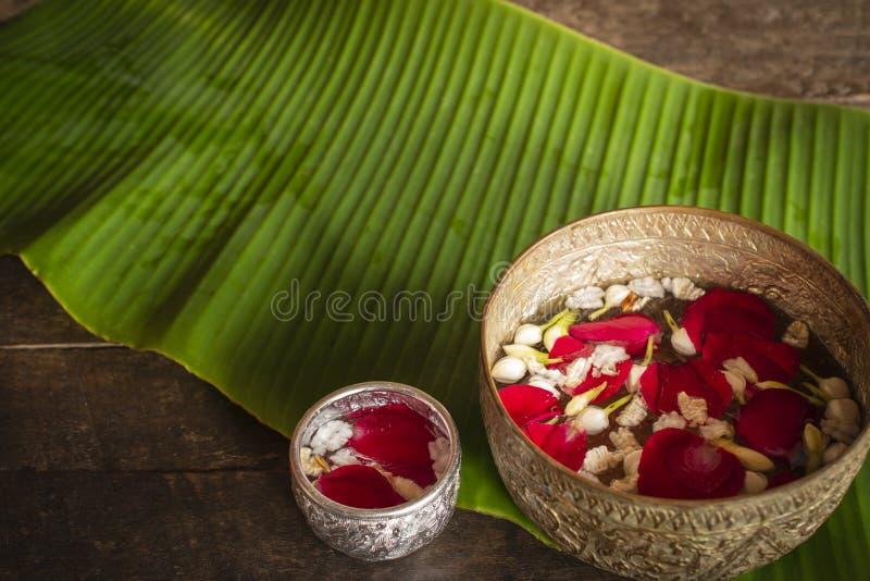 Den röda rosen, jasmin och poppade ris på den lugna vattenyttersidan som förläggas på trätabellen som är klar för, häller vatten  arkivbild