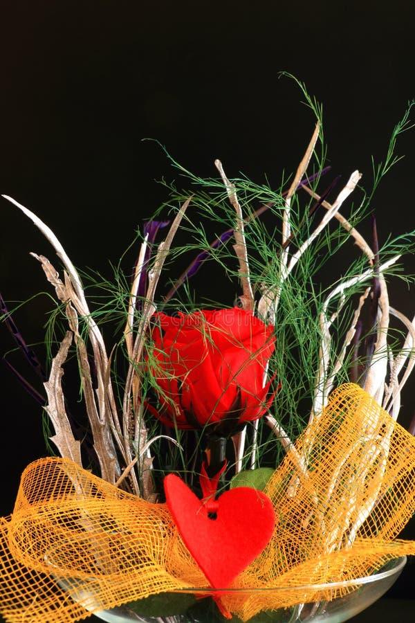 Den röda rosen smyckade med en ögla och en hjärta arkivbild
