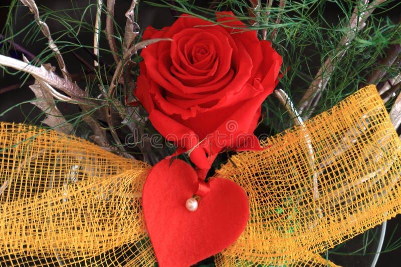 Den röda rosen smyckade med en ögla och en hjärta arkivfoto