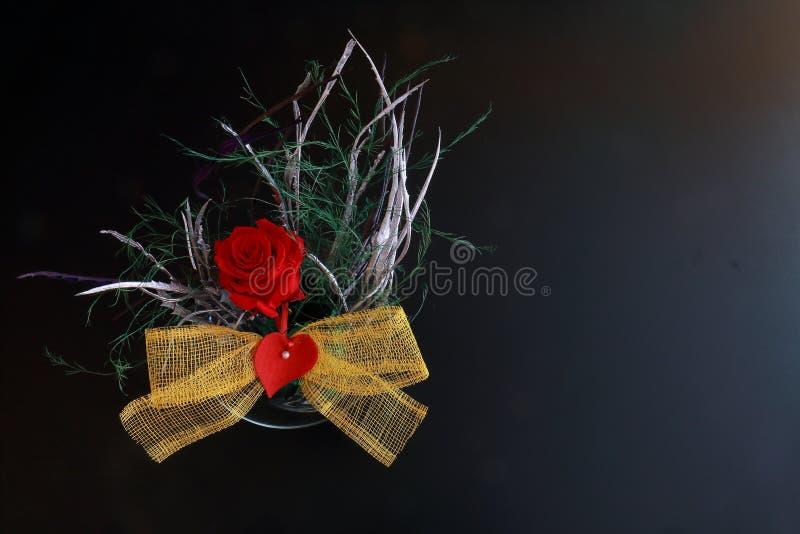 Den röda rosen smyckade med en ögla och en hjärta royaltyfri bild